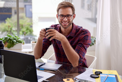 Fotografia  Young professional holding coffee and smiling at his desk