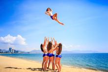 Cheerleaders Performs Stunt Basket Toss On Beach Against Resort