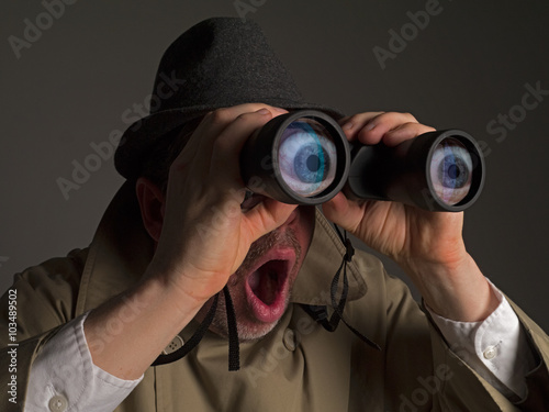 Fotografía  Photograph of a man in trench coat and hat looking through binoculars with huge, cartoonish eyes seen in the lenses
