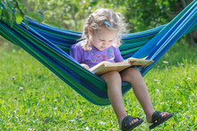 Concentrated Two Years Old Girl Reading Opened Book On Hanging Hammock In Green Summer Garden Outdoors