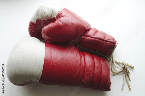 Fotografiet  old red and white boxing gloves on a light background