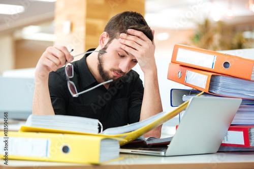 Fotografia  Sad businessman sitting at the table with many folders