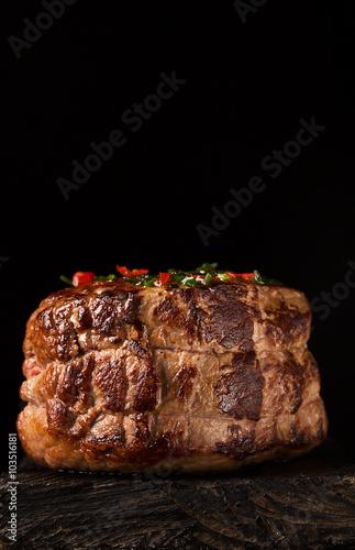 Obraz na plátne  Grilled Steak Meat on the wooden surface