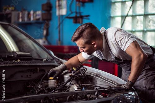 Car mechanic repairing vehicle Fototapeta