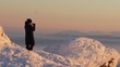 Woman watching the sunrise from the top of Are, Sweden mountain and taking photos of the beautiful panoramic view