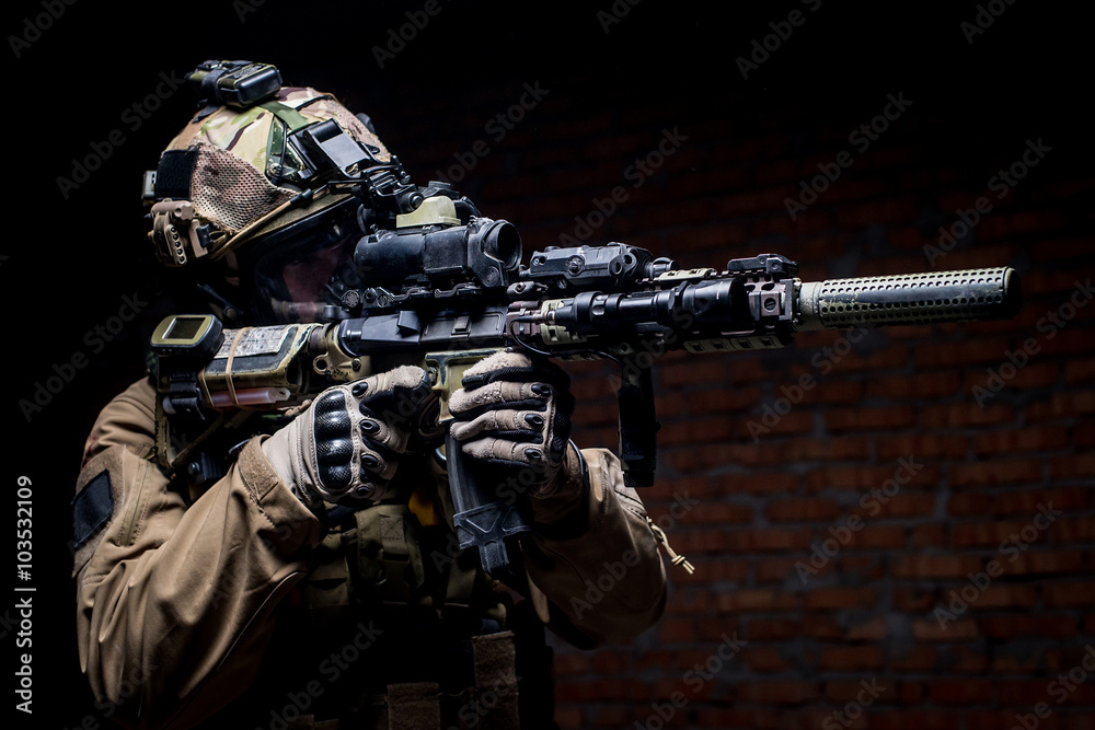 Fototapeta Spec ops soldier in uniform with assault rifle/man in military uniform with assault rifle aiming at target on background of dark wall