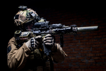 Fototapeta Militaria Spec ops soldier in uniform with assault rifle/man in military uniform with assault rifle aiming at target on background of dark wall