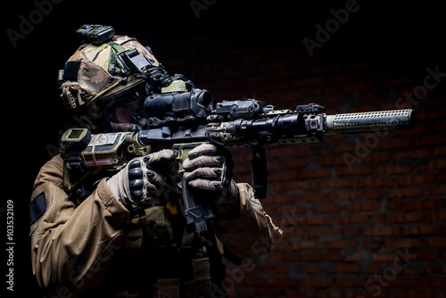 Foto  Spec ops soldier in uniform with assault rifle/man in military uniform with assa