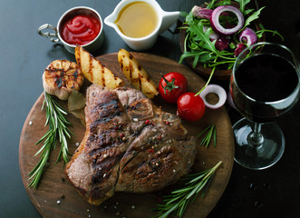 Fototapeta Do steakhouse Grilled meat T-Bone with vegetables, spices and glass of wine