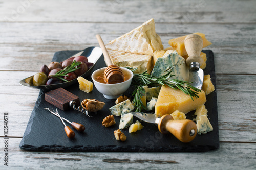 Fotografia  Delicious cheeses on a board with honey, nuts on a white backgro