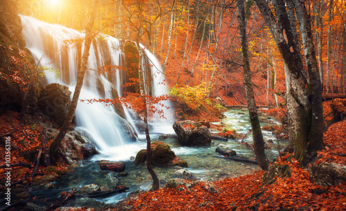 Fototapeten Wasserfalle Beautiful waterfall at mountain river in colorful autumn forest with red and orange leaves at sunset. Nature landscape
