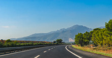 Sunshine On Fresh Black Tarmac On A Coastal Highway Running Through The Foothills And Mountain Ranges Of Continental Europe In Spain.  Road To Madrid.