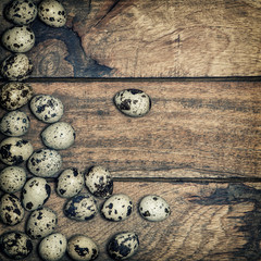 Quail eggs on wooden background. Vintage toned