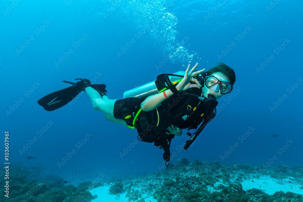 Fototapeta Female scuba diver underwater showing ok signal