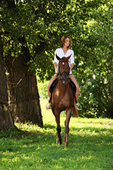 Portrait cowgirl with bay saddle horse in evening woods