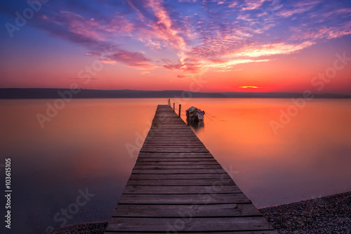 Photographie  Magnificent long exposure sunset with wooden pier and boat.