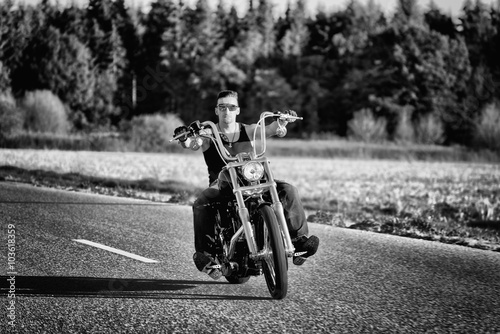 Photographie Tough, tattooed biker with his chopper in motion on the road