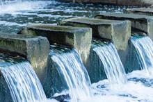 The Water Stream Flows Through A Concrete Dam