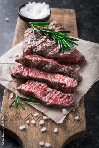 Fotografering  Grilled beef steak with rosemary and salt on cutting board