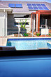 A view of a modern swimming pool and a house with solar panels o