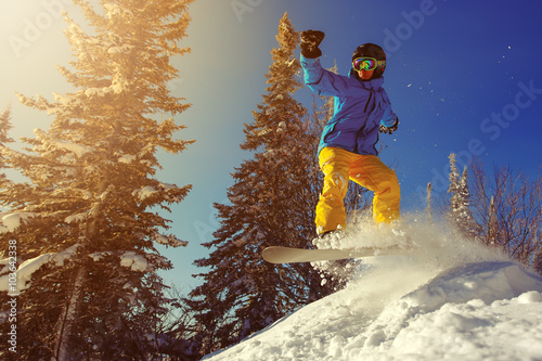Fotografia  Snowboarder jumping through air with deep blue sky in background