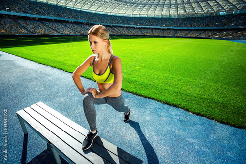 plakat Young sportswoman is at large modern stadium