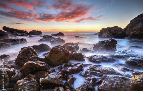 Beautiful sunrise on rocky shore and dramatic sky clouds