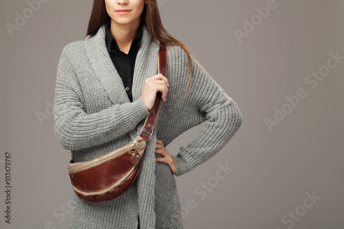Fotografía  Elegant model in gray woven cardigan with a leather fanny pack
