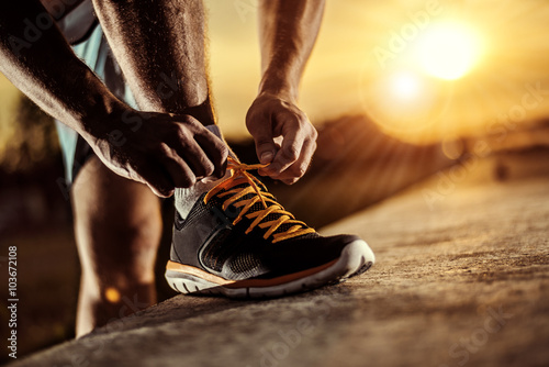 Staande foto Jogging Man tying jogging shoes