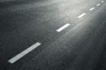 White dotted line on city asphalt road background.