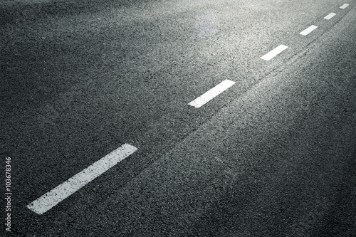 Fotografering White dotted line on city asphalt road background.