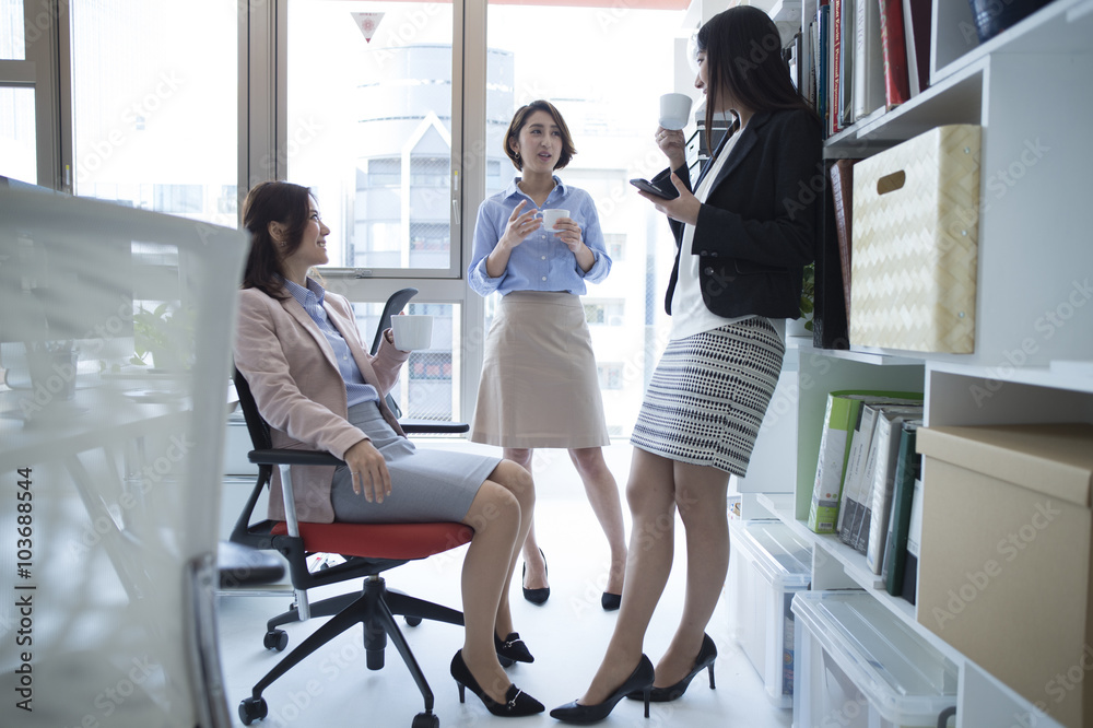 Fototapeta Three women are the stand talking in break time in the office