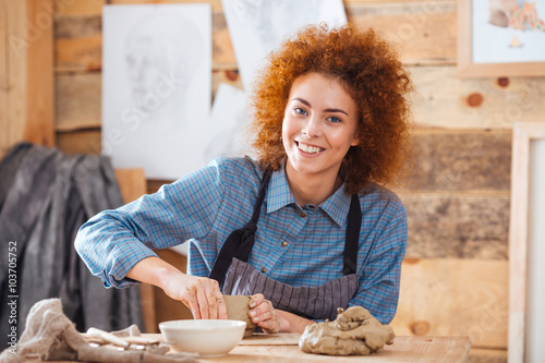 Cheerful woman potter sitting and working in art pottery studio