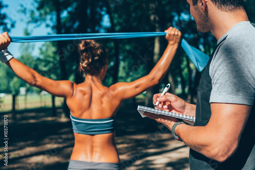 Exercising with personal trainer. Toned image