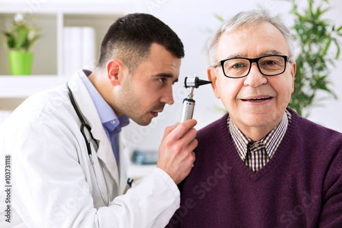 Doctor holding otoscope and examining patient ear Canvas Print