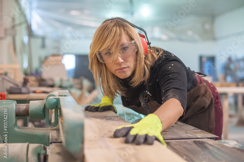 Obraz Female carpenter Using Electric Sander / Female carpenter Using Electric Sander for wood - fototapety do salonu
