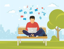 Young Man Sitting In The Park On The Bench And Working With Laptop