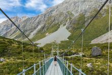 Woman Hiker Walking On Suspension Bridge