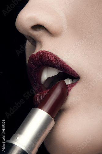 Woman applying red lipstick on black background