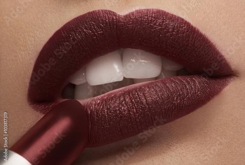 Fotografie, Obraz  Applying red lipstick on lips in close up photo