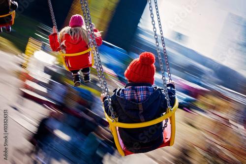 Papiers peints Attraction parc Kids, having fun on a swing chain carousel ride