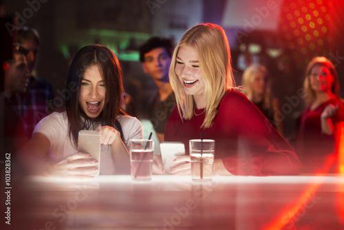 Fotografie, Obraz  Dvě mladé krásné dívky při pohledu na smartphone a smál