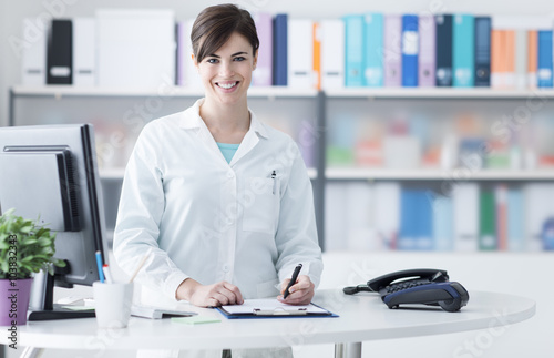 Smiling female doctor working at the clinic Poster