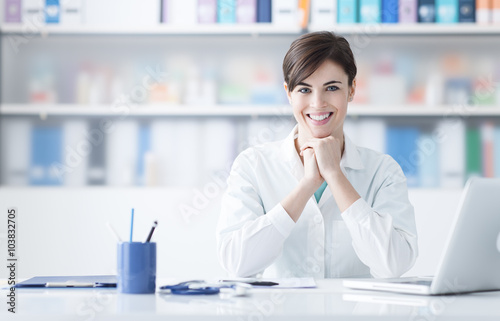 Doctor working at office desk Poster
