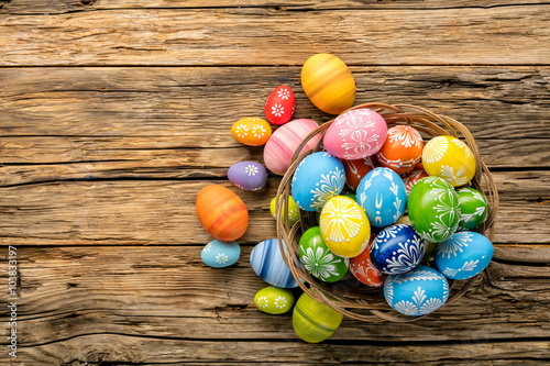 Easter eggs in basket placed on wooden planks Canvas Print