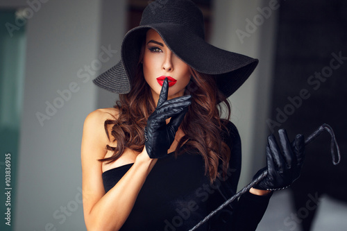 Fotografía  Sexy dominant woman in hat and whip showing no talk