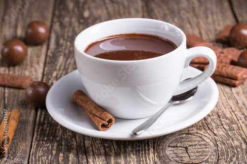 Spoed Foto op Canvas Chocolade White cup of delicious hot chocolate with candies on table.