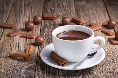 Foto op Canvas Chocolade White cup of delicious hot chocolate with candies on table.