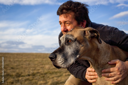 Fotografia, Obraz  Rugged man holding his great Dane in a windswept field with dramatic sky