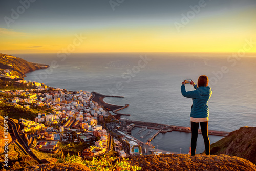 Fotografia  Young female traveler in blue jacket photographing Santa Cruz city standing on t